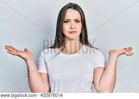 Young hispanic girl wearing casual white t shirt clueless and confused with open arms, no idea and doubtful face.
