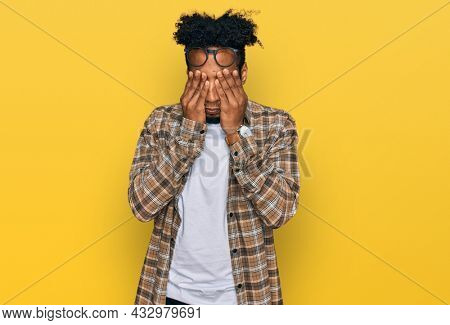 Young african american man with beard wearing casual clothes and glasses rubbing eyes for fatigue and headache, sleepy and tired expression. vision problem
