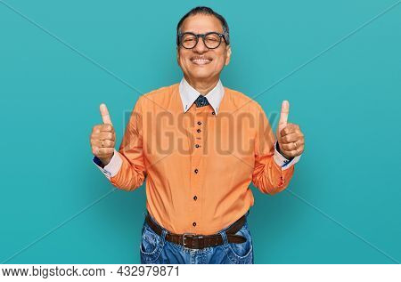 Middle age indian man wearing casual clothes and glasses success sign doing positive gesture with hand, thumbs up smiling and happy. cheerful expression and winner gesture.