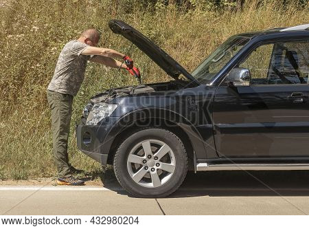 Man Standing With Mechanic Tool Near Car With Hood Up Outdoors In Summer And Repairing It After Car