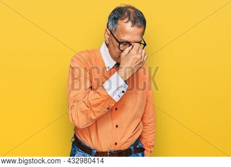 Middle age indian man wearing casual clothes and glasses tired rubbing nose and eyes feeling fatigue and headache. stress and frustration concept.