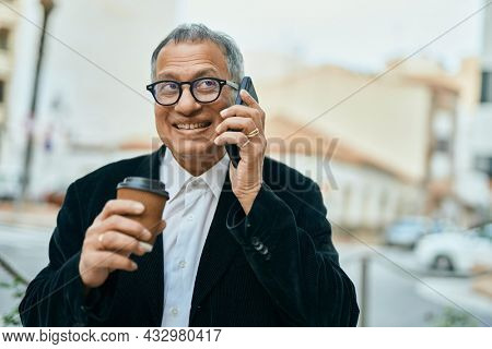 Middle age southeast asian man speaking on the phone and drinking a cup of coffee at the city