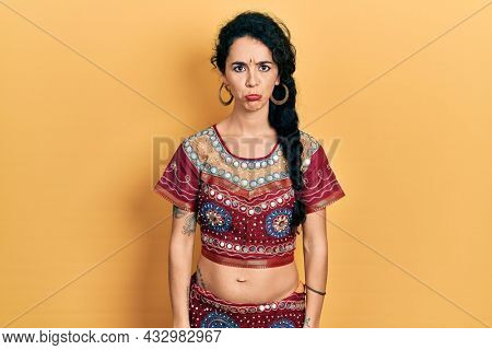 Young woman wearing bindi and bollywood clothing depressed and worry for distress, crying angry and afraid. sad expression.