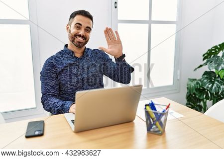 Young hispanic man with beard working at the office with laptop waiving saying hello happy and smiling, friendly welcome gesture