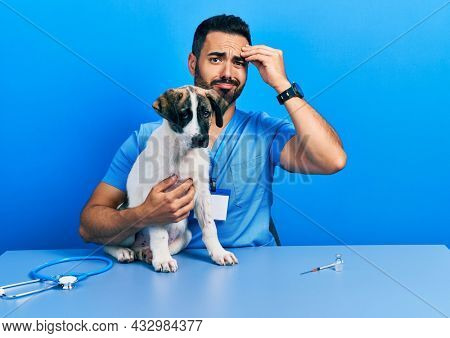 Handsome hispanic veterinary man with beard checking dog health worried and stressed about a problem with hand on forehead, nervous and anxious for crisis