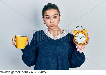 Young caucasian girl holding coffee and alarm clock puffing cheeks with funny face. mouth inflated with air, catching air.