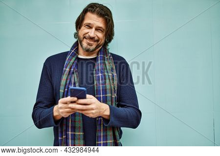 Middle age handsome man using smartphone leaning on the wall