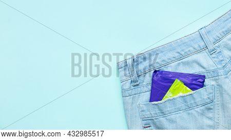 Menstruation Sanitary Pads In Packaging In Back Pocket Of Light Blue Jeans On Blue Background.femini