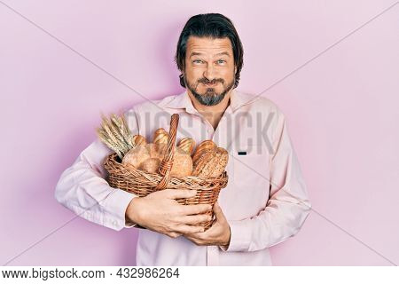 Middle age caucasian man holding wicker basket with bread puffing cheeks with funny face. mouth inflated with air, catching air.