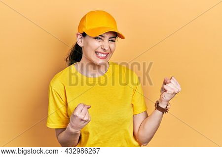 Young hispanic woman wearing delivery uniform and cap excited for success with arms raised and eyes closed celebrating victory smiling. winner concept.