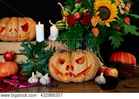 Halloween Concept: Pumpkins, Candles, Sunflower, Leaves, Lantern And Other Attributes At The Table A