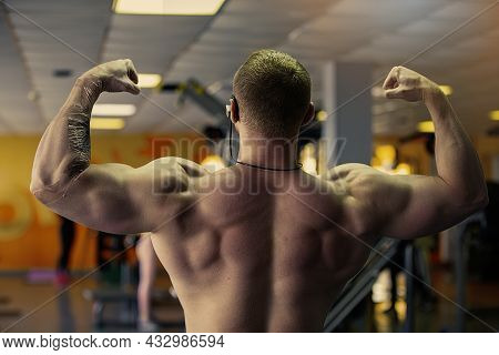 Athletic Men Show Biceps And Triceps On Their Back.