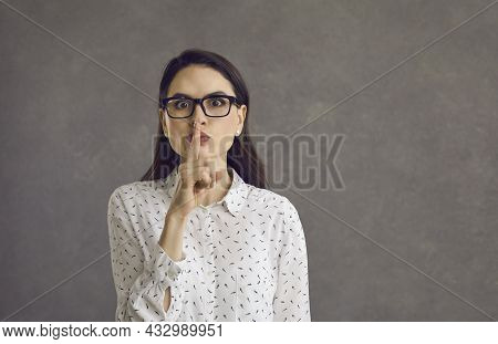 Young Woman With A Serious Expression Demands Silence Or Quiet Or Asks To Keep A Secret.