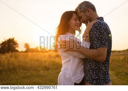 Beautiful Middle-aged Couple In Nature. Romance And Love At Sunset