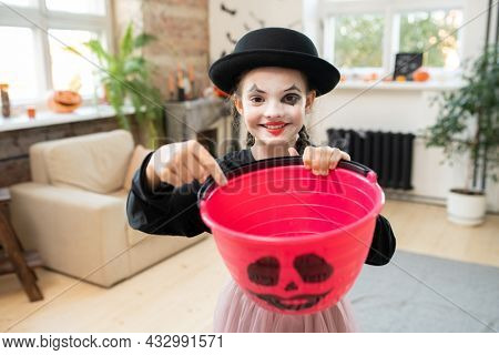 Adorable girl in halloween attire pointing at empty bucket for treats while looking at you