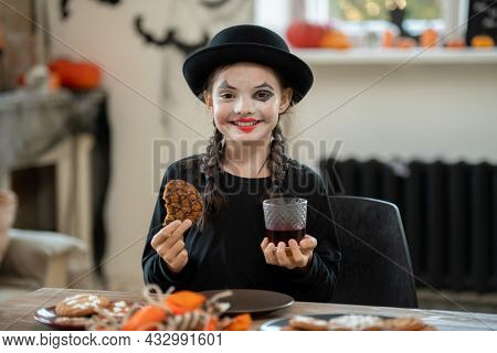 Happy girl in halloween attire having cookie and drink while sitting by festive table