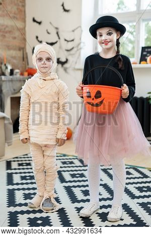 Two kids in halloween attire standing in front of camera in home environment