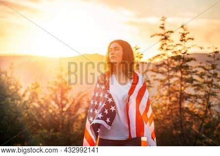 Independence Day And Memorial Day. Caucasian Young Woman Wrapped In American Flag. Sunset In The Bac
