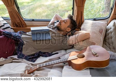 Tired young man napping or daydreaming on bed inside house on wheels on summer day