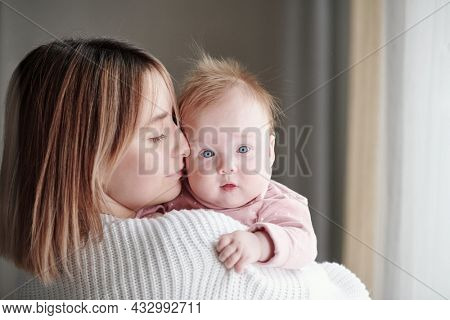 Young affectionate woman touching face of her cute baby daughter in front of camera