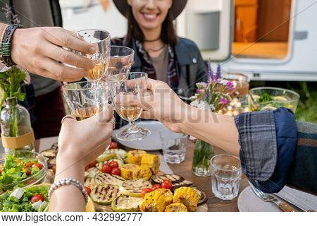 Hands of several friends clinking with glasses of wine by served festive table