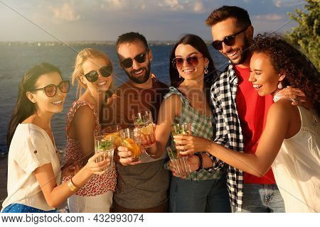 Group Of Friends With Drinks Having Fun Near River At Summer Party