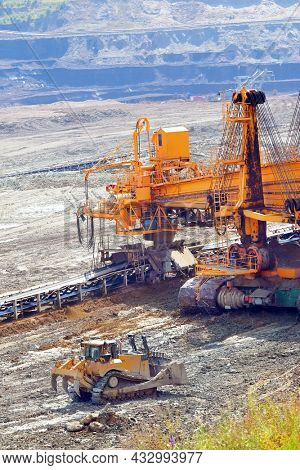 Bucket wheel excavator and bulldozer at work in coal mine. Mining industry from above. Open pit in Central Europe. Heavy industry before Green deal.