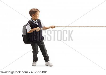 Full length profile shot of a little schoolboy pulling a rope isolated on white background