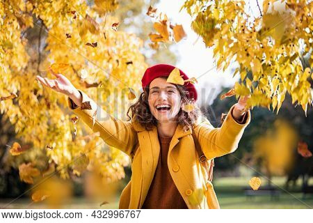 Beautiful young woman throwing autumn yellow leaves. Portrait of joyful woman playing with leaves in park during fall. Happy girl wearing coat and red beret playing with yellow leaves outdoor.
