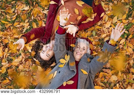 Senior grandmother and smiling granddaughter lying on yellow and red leaves at park, view from above. Top view of playful old woman with cheerful girl lying on autumn park leaves, looking at camera.