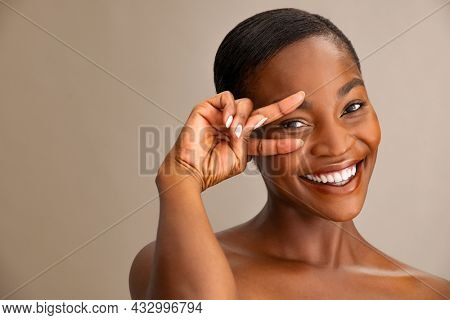 Portrait of smiling mature woman with perfect skin showing victory sign near eye on brown background. Close up face of african woman showing successful results after anti-aging wrinkle treatment.