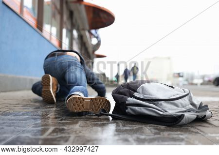 Man With Backpack Lying On Slippery Sidewalk After Fall Closeup