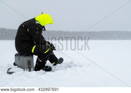 Winter Fishing On Ice. Man Jiggling Bait In An Ice Hole. Relaxing In The Wild During Snowfall.