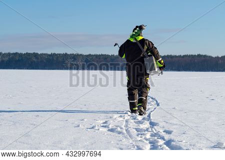 Man With Fishing Equipment Walking On A Frozen Lake Into The Distance On A Sunny Winter Day.