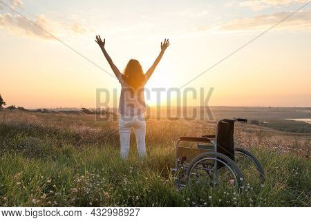 Woman Standing Near Wheelchair In Evening Outdoors, Back View. Healing Miracle