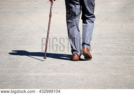 Man Walking With A Cane On A Street, Male Legs In Trousers On Sidewalk. Concept Of Disability, Limpi