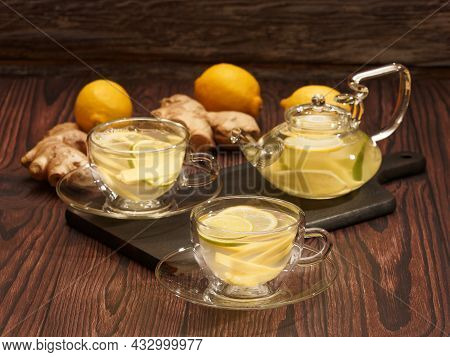 Ginger And Lemon Tea In Glass Cups And Teapot On A Burned Wood Cutting Board