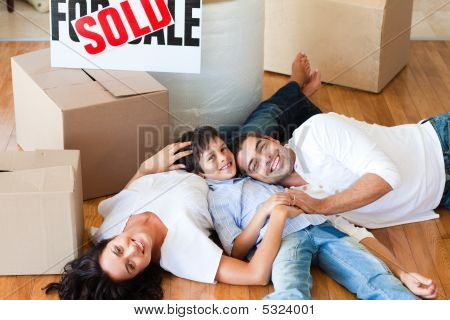Parents And Son Moving House Lying On Floor