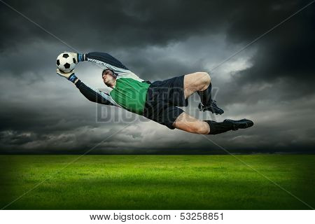 Football goalman with ball in action outdoors