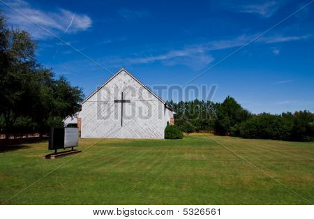 Old Church In Field With Empty Sign And Cross