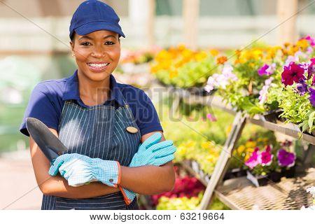 beautiful black nursery worker in greenhouse