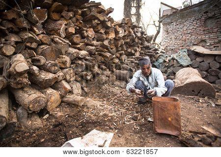 KATHMANDU, NEPAL - DEC 19, 2013: Unidentified a man sort wood for cremation rites in Bhasmeshvar Ghat at Pashupatinath temple in Kathmandu.