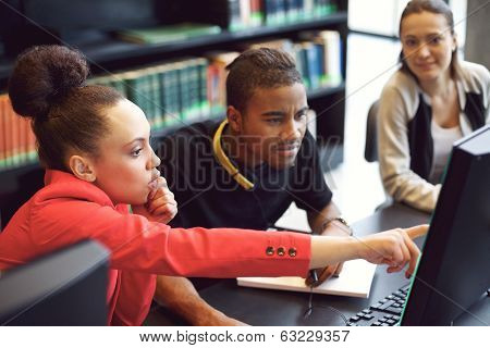 Group Of Students Doing Online Research In Library