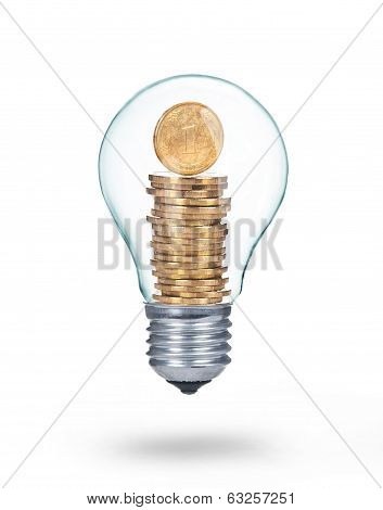 Traditional light glass bulb with golden coins isolated on white