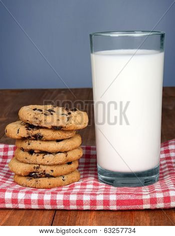 Glass of milk and cookies on wooden table on bue background