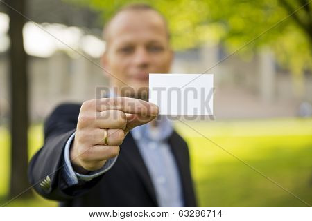 Business man presenting a business card, standing outdoors on the grass in front of a convention center. Focus on the hand and business card