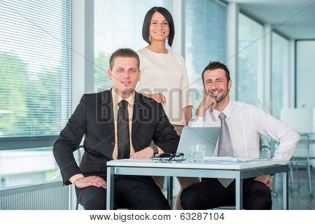 Three coleagues posing in modern office