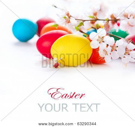 Easter. Colorful Easter eggs with spring blossom flowers isolated over white background. Colored Egg Holiday border art design