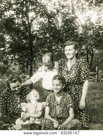 LODZ, POLAND, CIRCA 1950's: Vintage photo of grandmother and parents with children in garden