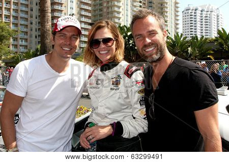 LOS ANGELES - APR 12:  Michael Trucco, Tricia Helfer, JR Bourne at the Long Beach Grand Prix Pro/Celeb Race Day at the Long Beach Grand Prix Race Circuit on April 12, 2014 in Long Beach, CA